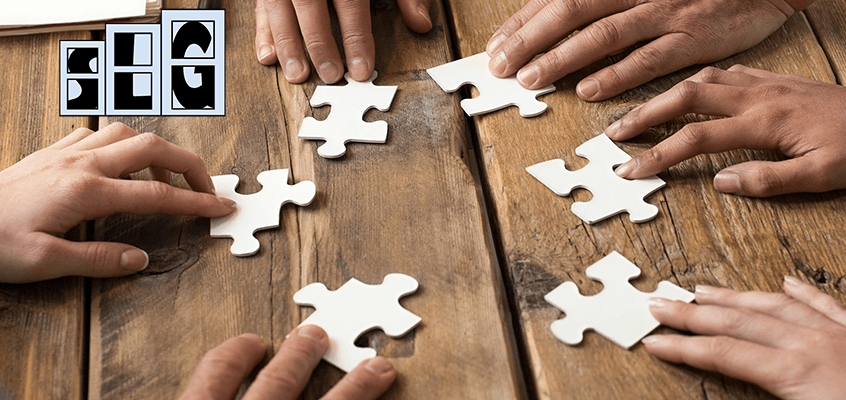 5 people with puzzle pieces playing a cooperative game