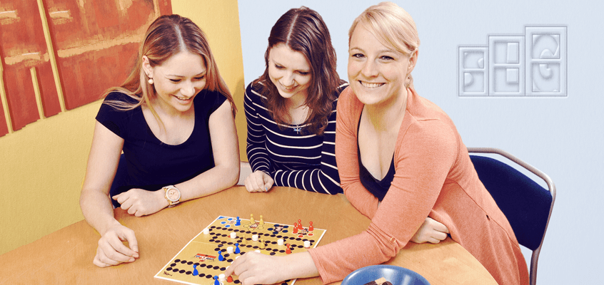 Three Women Playing a Board game and Smiling