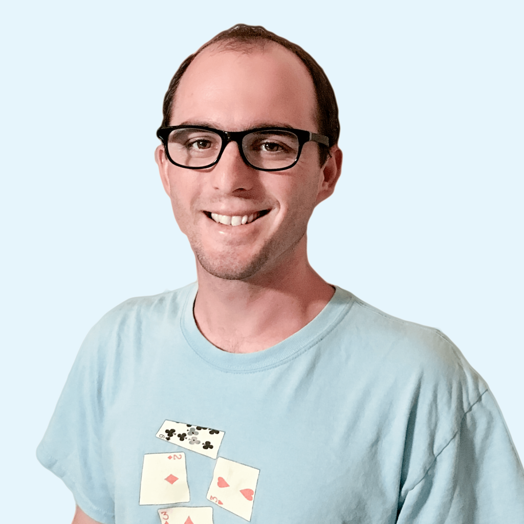 Photo of Calvin Keeney of Streamlined Gaming with a light blue background and a blue tshirt with playing cards on it