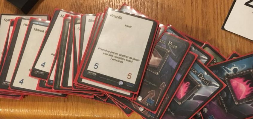 Old sleeved trading cards on the table with newly printed monster cards for Memaws Monsters Tower Defense prototype by Calvin Keene