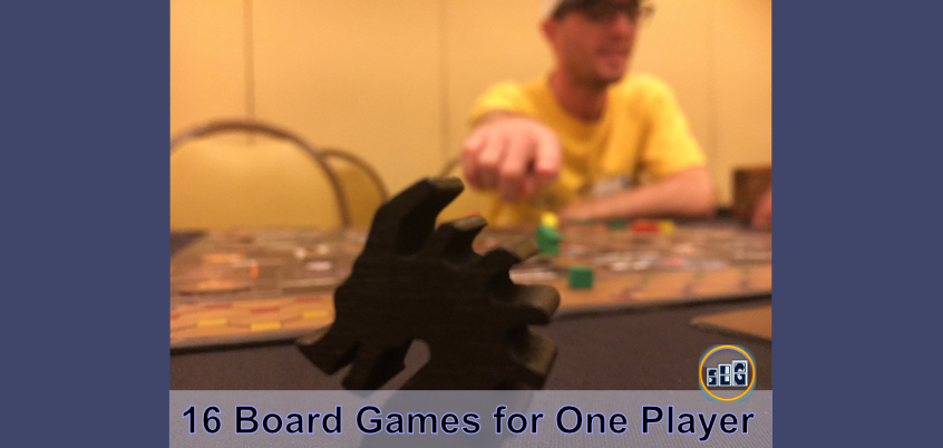 Calvin Keeney pointing at a wooden Black Dragon as he plays a fun board game that has a great single player mode for solo board gamers